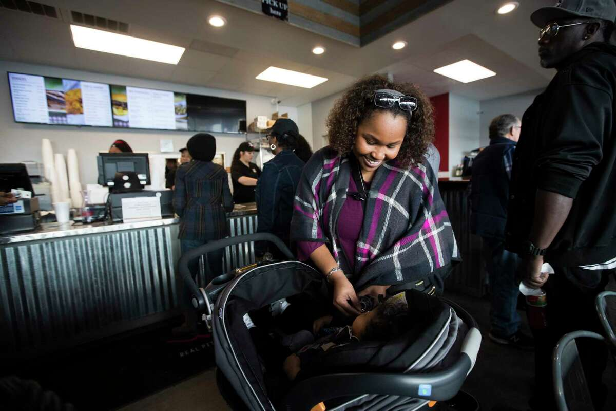 A furloughed federal worker who didn't wish to be identified gives water to her baby while waiting to be served with a family meal provided by Ray's BBQ Shack for free on Monday, Jan. 21, 2019, in Houston. The bbq restaurant announced that from 1 p.m. to 4 p.m. on Monday, Jan. 21, 2019, in Houston, furloughed federal workers are welcomed to pick up a meal for free.