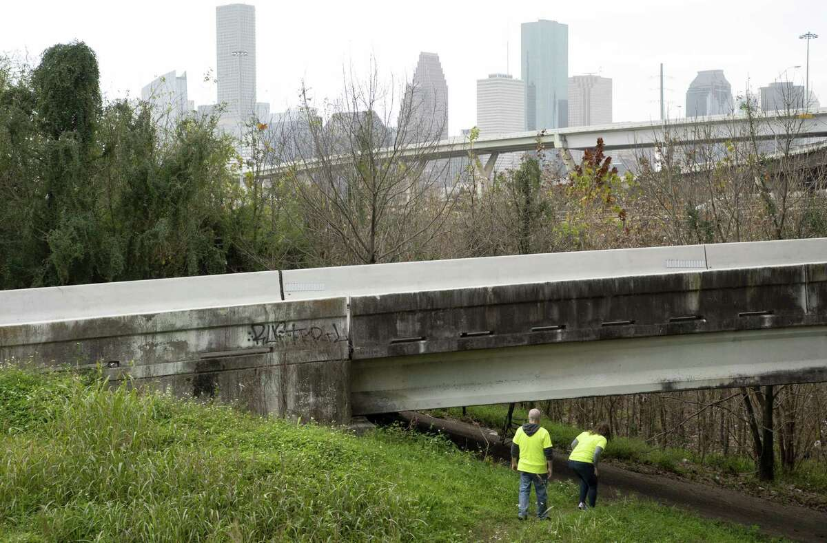 Harmony House CEO Meg Pohodich and Preston Witt make their way down to the space under an overpass where they know two homeless men stay as they surveyed the homeless population Tuesday, Jan. 22, 2019, in Houston.