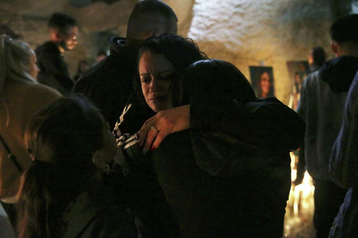 Monica Perez hugs her daughter, Isabella Amescua, 15, during a vigil for Nichol Olsen and her two daughters at the Oblate Mission Lourdes Grotto last week. Olsen, 37, a local hairstylist, and her daughters, Alexa Montez, 16, and London Sophia Bribiescas, 10, who were found shot dead at a home near Leon Springs on Jan. 10.