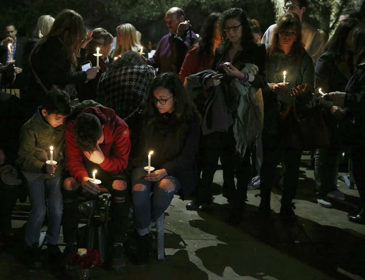 Friends and family mourn during a vigil for hairstylist Nichol Olsen and her two daughters at the Oblate Mission Lourdes Grotto last week. Olsen, 37, and her daughters, Alexa Montez, 16, and London Sophia Bribiescas, 10, were found shot to death at a luxury home in far northwest Bexar County on the morning of Jan. 10.