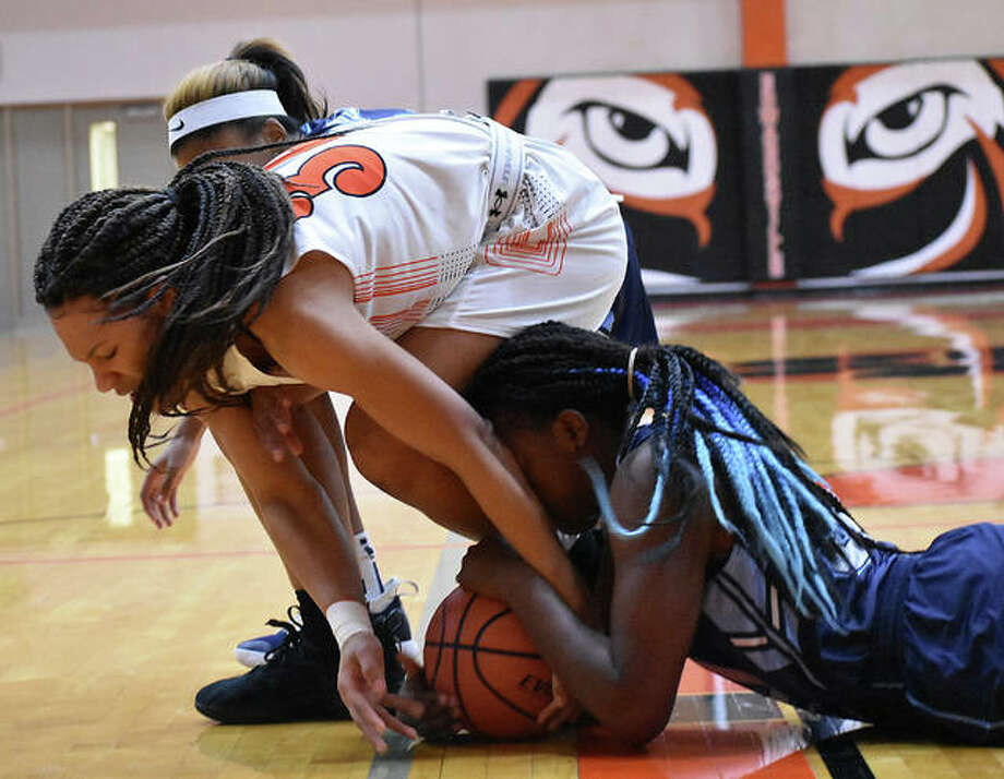 Edwardsville junior forward Maria Smith, top, battles for a loose ball with a Belleville East player during the first quarter Tuesday inside Lucco-Jackson Gymnasium. Photo: Matt Kamp/Intelligencer