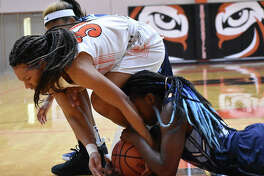 Edwardsville junior forward Maria Smith, top, battles for a loose ball with a Belleville East player during the first quarter Tuesday inside Lucco-Jackson Gymnasium.