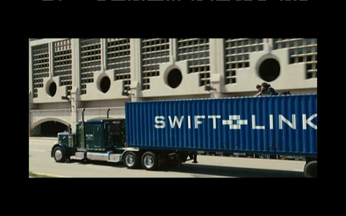 On Water Street, with Angelina Jolie on the back of a truck as it passes a parking garage that is behind the James T. Foley Federal Courthouse at 445 Broadway.