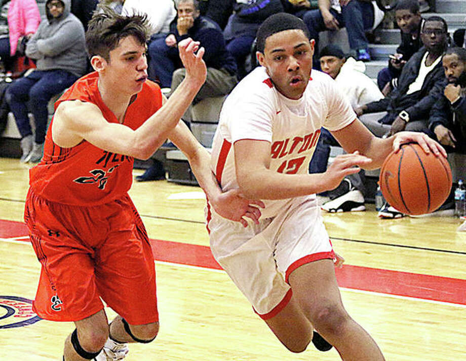 Alton's Josh Rivers (right) drives the baseline on Edwardsville's Brennan Weller on Tuesday night in a Southwestern Conference boys basketball game at Alton High in Godfrey. Photo: Greg Shashack   The Telegraph