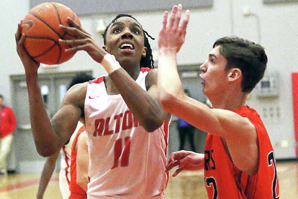Alton's Donovan Clay (left) goes to the basket while Edwardsville's Brennan Weller defends Tuesday night in a Southwestern Conference boys basketball game at Alton High in Godfrey.