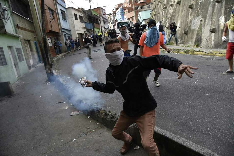 A demonstrator throws back a tear gas canister during a protest in the Cotiza neighborhood of Caracas, Venezuela, on Jan. 21, 2019. Photo: Bloomberg Photo By Carlos Becerra. / © 2019 Bloomberg Finance LP