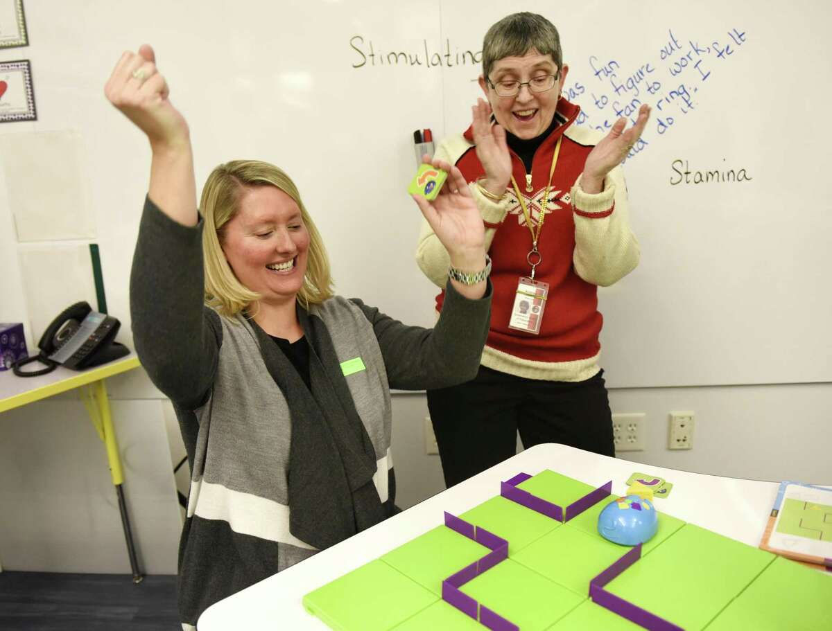 Erica Westfall, left, and Andrea Casson Vaz celebrate after successfully programming a mechanical mouse to reach its cheese during the Design Lab launch at Glenville School Tuesday. The Design Lab, an extension of the school's Media Center, features a variety of STEM activities for students to explore.