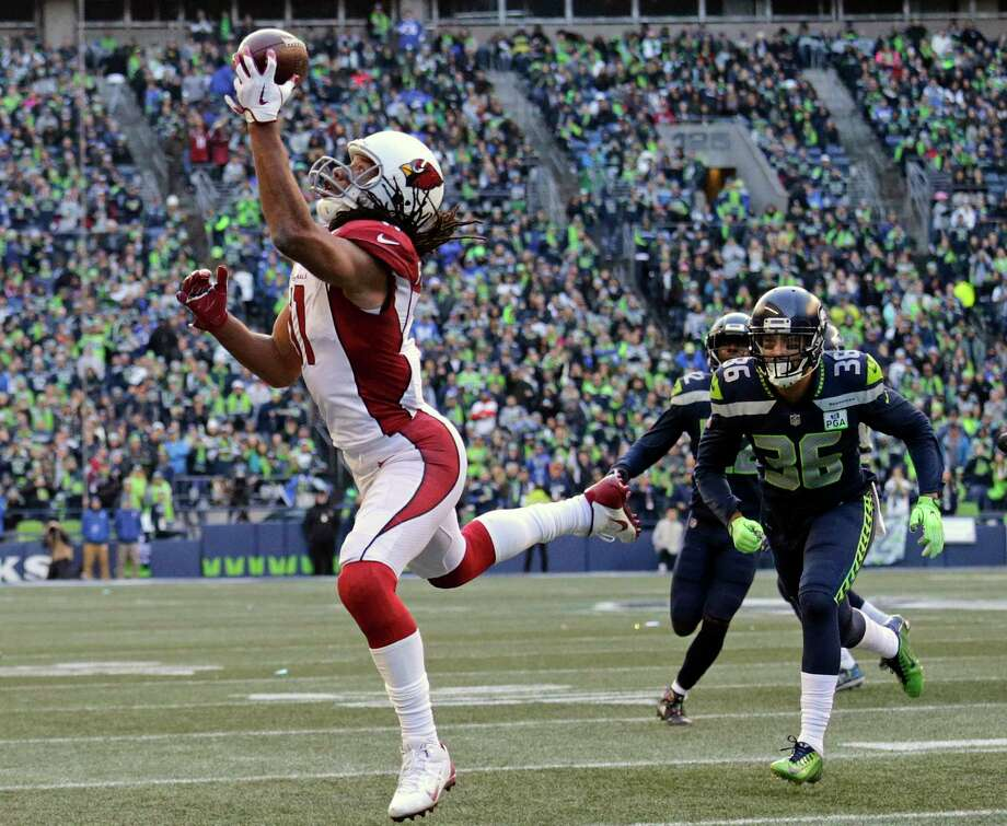 """FILE - In this Dec. 30, 2018, file photo, Arizona Cardinals' Larry Fitzgerald, left, snags a one-handed touchdown pass against the Seattle Seahawks during the first half of an NFL football game, in Seattle. Star receiver Larry Fitzgerald is returning to the Arizona Cardinals for a 16th NFL season. The Cardinals announced Wednesday, Jan. 23, 2019, that they signed the 35-year-old Fitzgerald to a one-year contract. Team president Michael Bidwell says, """"No player has meant more to this franchise or this community than Larry Fitzgerald."""" Photo: John Froschauer, AP / Copyright 2018 The Associated Press. All rights reserved."""