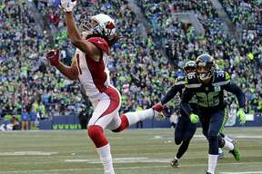 "FILE - In this Dec. 30, 2018, file photo, Arizona Cardinals' Larry Fitzgerald, left, snags a one-handed touchdown pass against the Seattle Seahawks during the first half of an NFL football game, in Seattle. Star receiver Larry Fitzgerald is returning to the Arizona Cardinals for a 16th NFL season. The Cardinals announced Wednesday, Jan. 23, 2019, that they signed the 35-year-old Fitzgerald to a one-year contract. Team president Michael Bidwell says, ""No player has meant more to this franchise or this community than Larry Fitzgerald."""