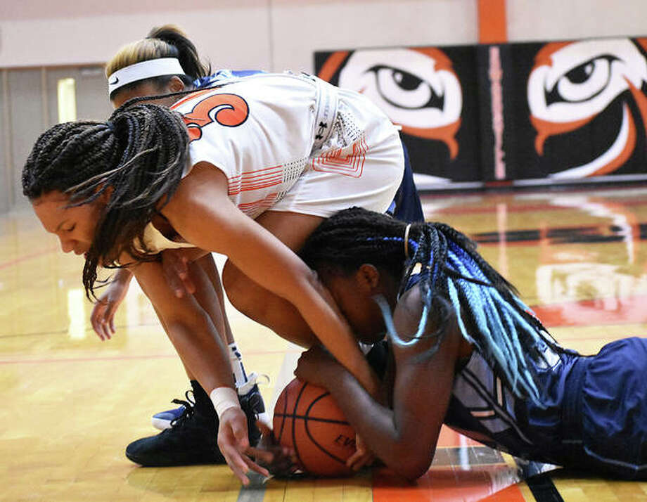 Edwardsville's Maria Smith (top) battles for a loose ball with a Belleville East player during the first quarter Tuesday night in Edwardsville. Photo: Matt Kamp / Hearst Illinois