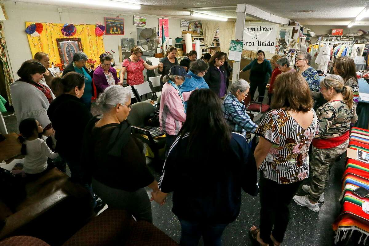 Members of Fuerza Unida, an organization led by South Side women, hold hands in prayer while celebrating their 29th year of fighting for environmental, economic and social justice at their headquarters on New Laredo Highway on Tueday, Jan. 22, 2019.