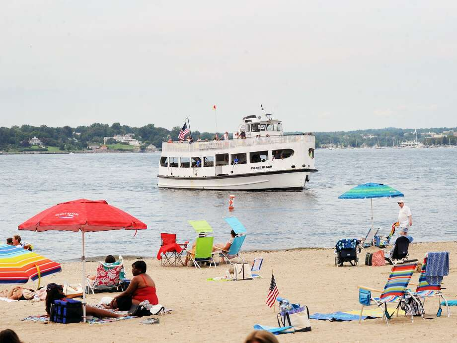 As people enjoy the beach, the Island Beach ferry nears the dock at Island Beach off the coast of Greenwich, Conn., Saturday, August 25, 2018, on the day a ceremony was held commemorating the 100th anniversary of when the island, that is used as a public beach, was donated to the Town of Greenwich in 1918. Photo: Bob Luckey Jr. / Hearst Connecticut Media / Greenwich Time