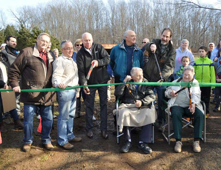 Helping with the ribbon cutting for the North Branford Land Trust, from left, are Roger Salway, State Rep. Vincent Candelora, Mayor Michael Doody, Attorney Ted Fretel, and David Sargent, President of NBLCT. Seated are Dudley and Vicky Harrison. Photo: Contributed Photo