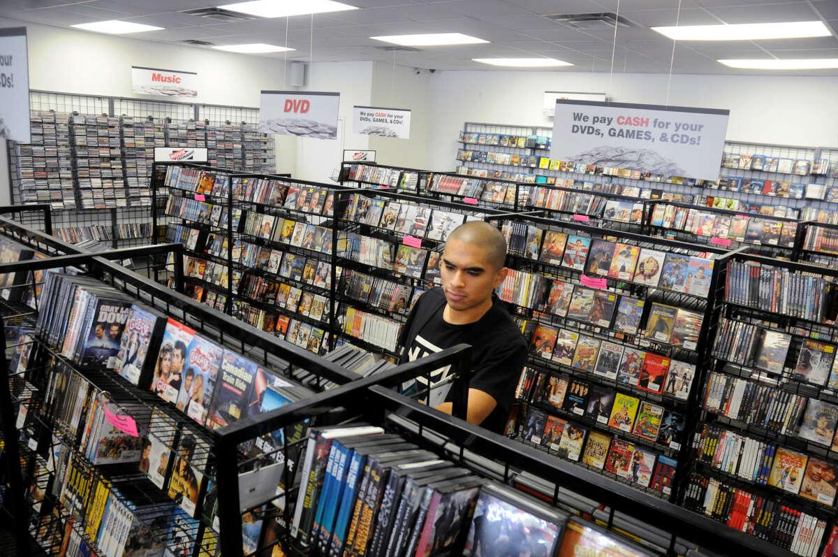 Jonathan Portillo straightens the shelves at Movie Exchange.