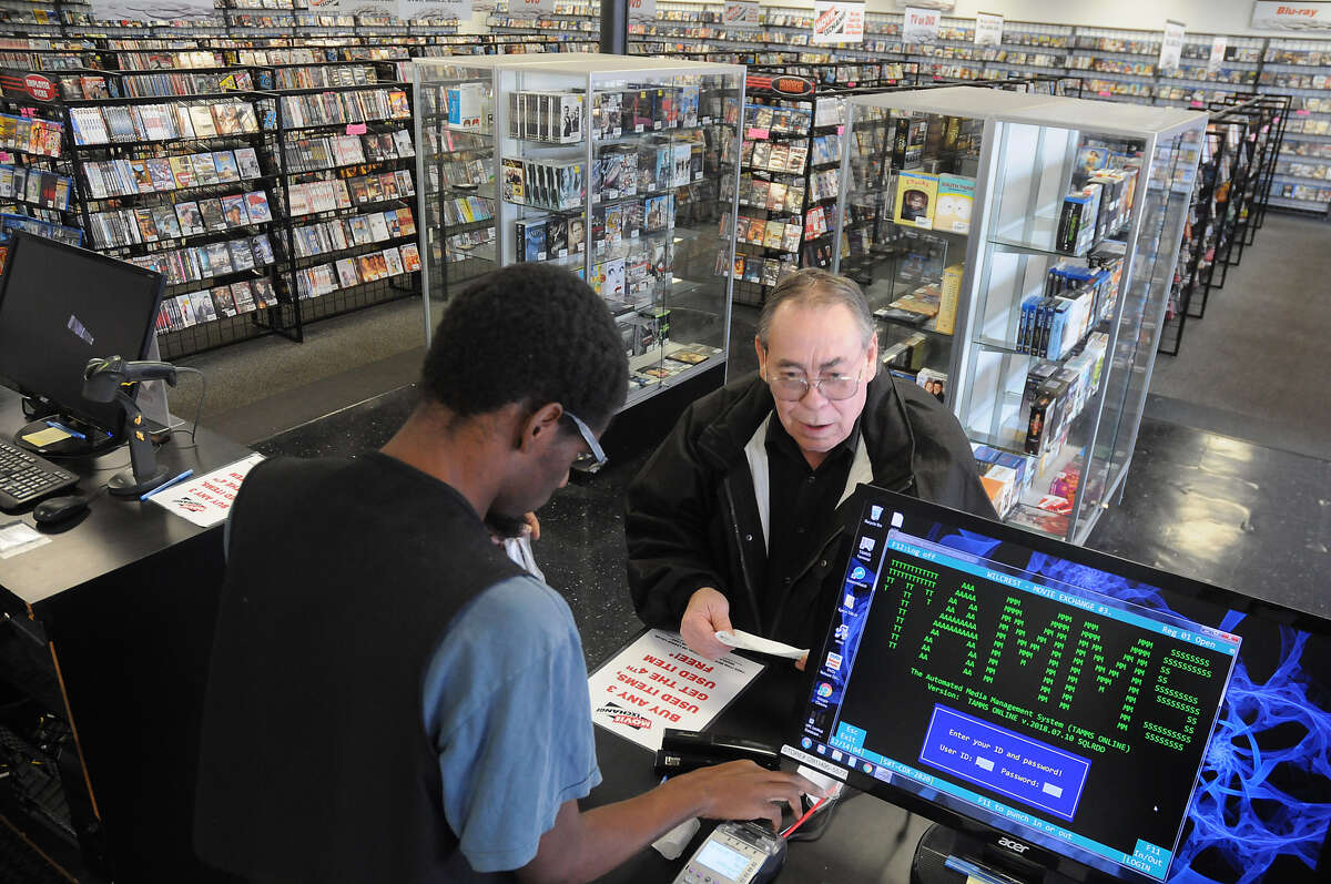 Regular customer Frank Logan buys a stack of DVD's from Xavier Readeaux at Movie Exchange at 11803 Wilcrest