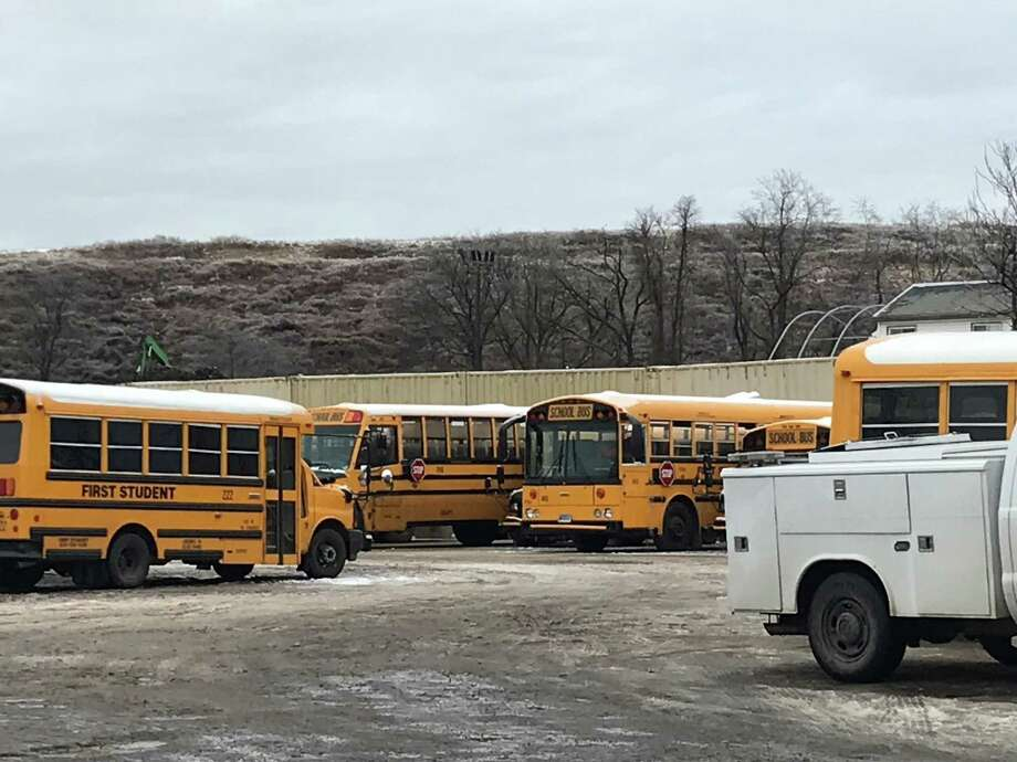 Several buses coated in snow and ice parked in the First Student bus depot on Middletown Avenue. Photo: Brian Zahn / Hearst Connecticut Media