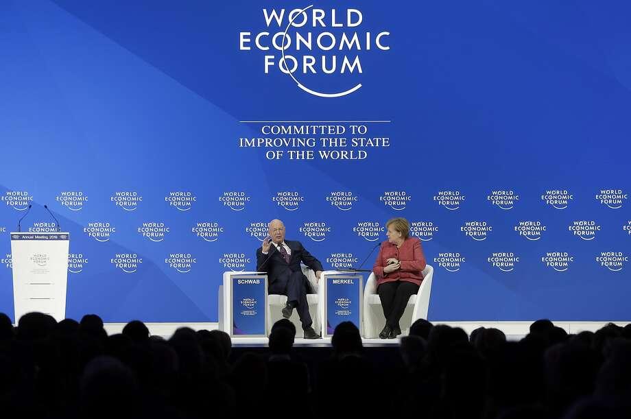 Klaus Schwab, executive chairman of the World Economic Forum, talks with German Chancellor Angela Merkel after she addressed the annual meeting in Davos, Switzerland. Photo: Markus Schreiber / Associated Press