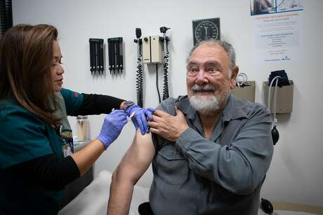 Ilda Villahermosa administers a flu shot to Eugene Thiers, 77, of San Mateo, at Kaiser Permanente Redwood City on Monday, Jan. 14, 2019, in Redwood City, Calif.