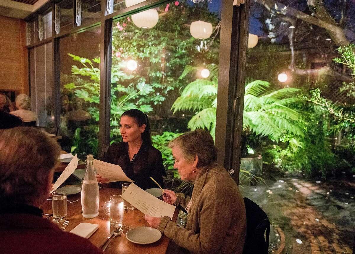 Customers look over the menu in the main dining room at Rivoli in Berkeley, Calif. Wednesday, Jan. 16, 2019.