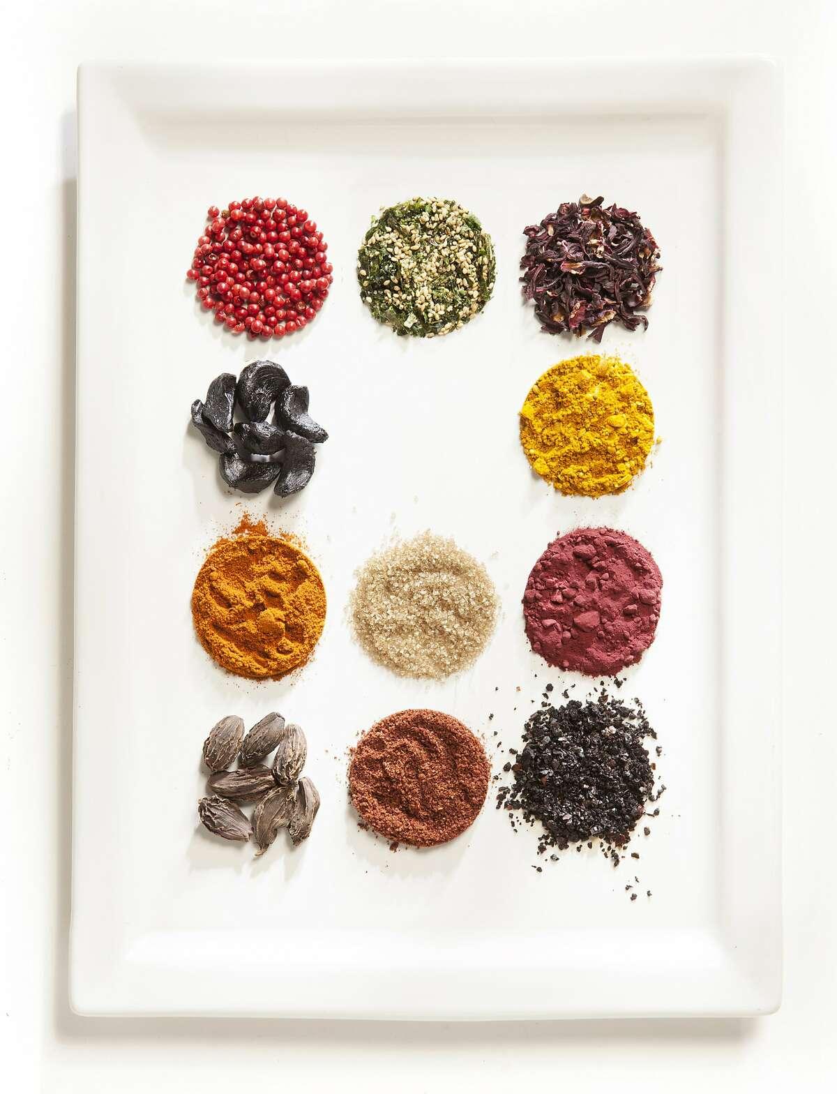 Spices, top row, from left: pink peppercorns, furikake, hibiscus flower. Second row: black garlic, vadouvan. Third row: Berbere, smoked salt, beet powder. Bottom row: black cardamom, sumac, Urfa biber
