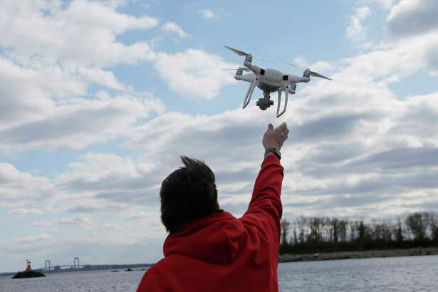 FILE - In this April 29, 2018, file photo, a drone operator helps to retrieve a drone after photographing over Hart Island in New York. Drone sightings reported by airline pilots over New Jersey renew questions about how to accommodate the popular devices into the nation's airspace. The ability of drones to interfere with aviation is likely to get worse as the number of machines multiplies. Many store-bought drones come with technology to prevent owners from flying them near airports, but there are hacks, and home-built machines don't necessarily include those protections.
