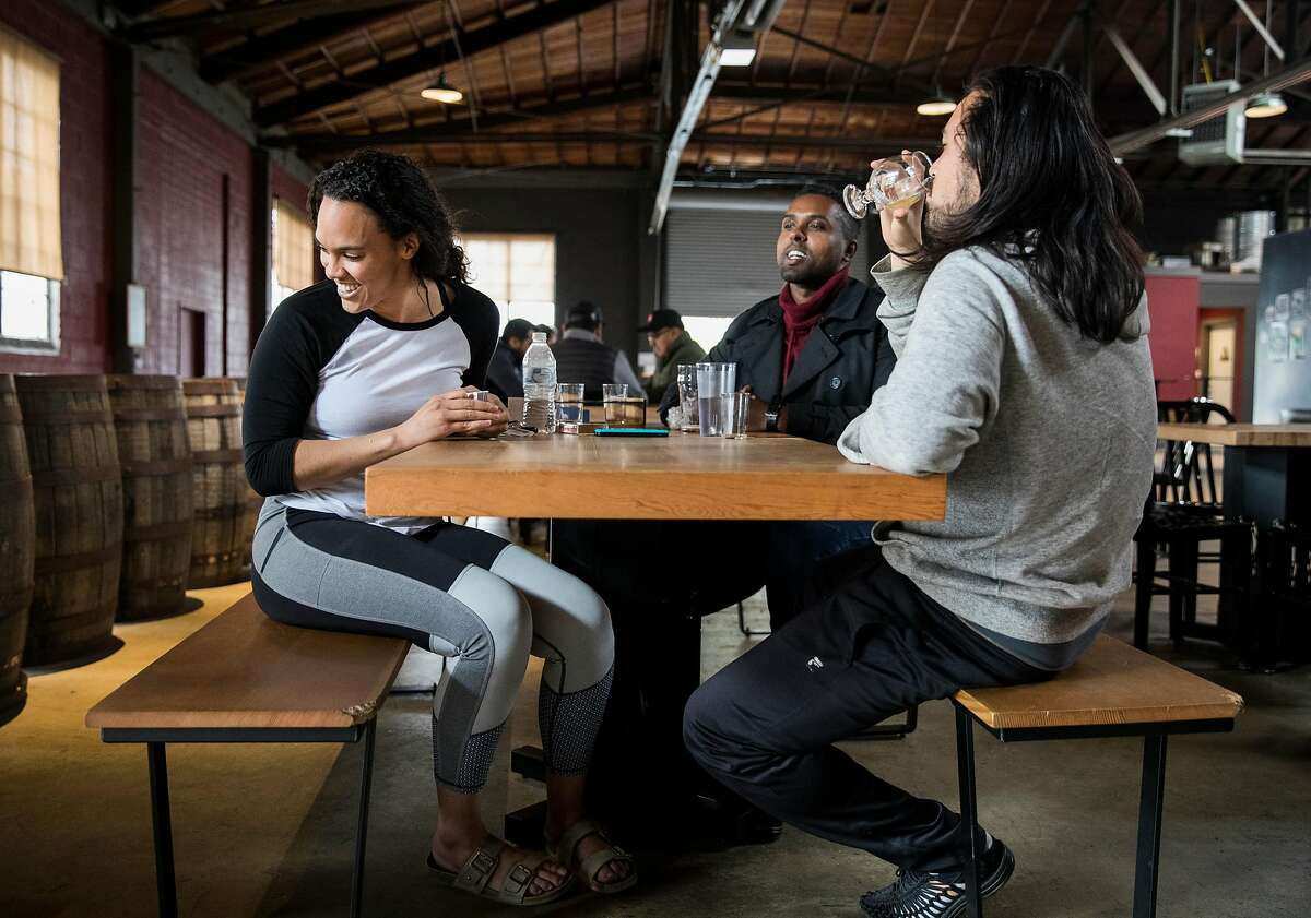 (From left) Dani Lane, Micael Sega and Chris Hamano chat over beers while hanging out at Ghost Town Brewing in Oakland, Calif. Friday, Jan. 18, 2019.
