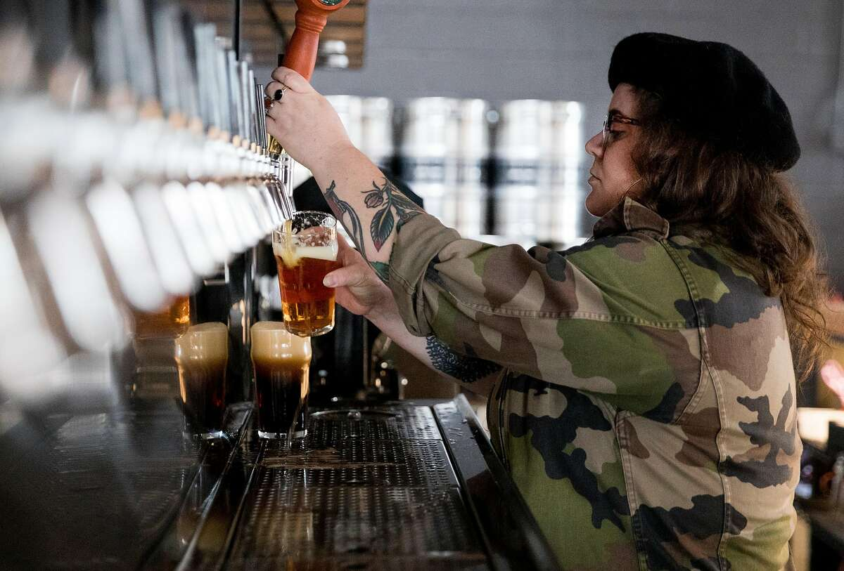 Bartender Kellianne Johnston pours beer for customers at Ghost Town Brewing in Oakland, Calif. Friday, Jan. 18, 2019.