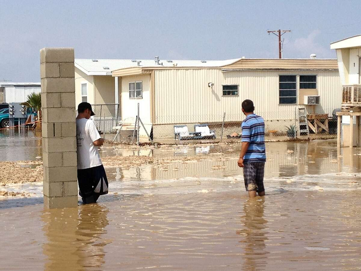 Two men stand in near knee deep water in a mobile home park in Mecca, Calif. after a sudden heavy rain flooded the area early , Tuesday, Sept. 11, 2012. Early morning thunderstorms over southeastern California's Coachella Valley has caused flooding in mobile home parks in Mecca and Thermal. The National Weather Service says more than 5 inches of rain fell in an area bounded by the Salton Sea communities of Oasis, Mecca and North Shore. More than 3 feet of water flooded Highway 111.