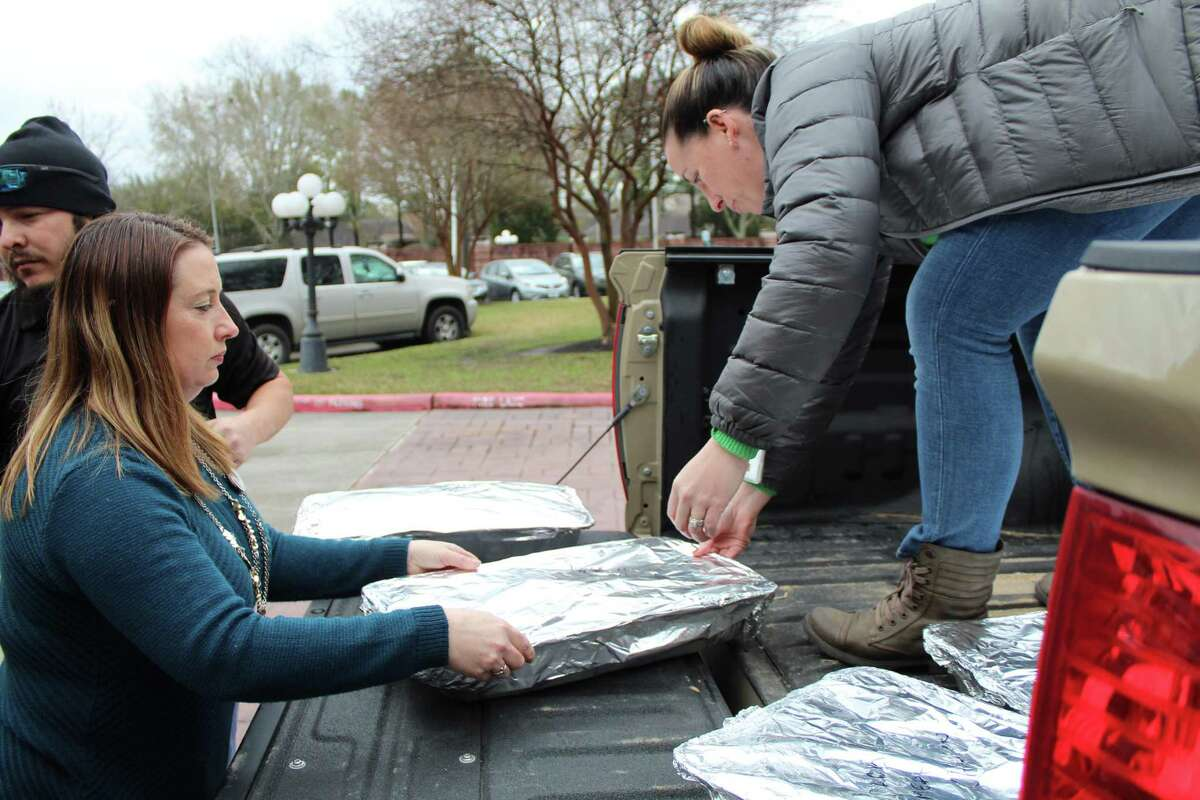 Arbor Terrace-Kingwood's Marketing Director Stacy Arceneux hands over a tray of food to Laura Vensel, an air traffic controller on Jan. 23, 2019.