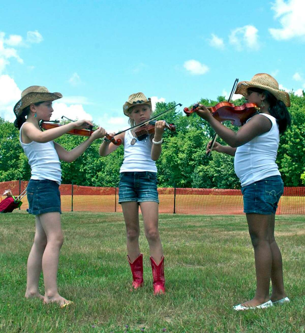 SPECTRUM/Tuning up for their performance are, from left to right, Jenna Hutensky, 8, of West Hartford, Abby Sowa, 9, of Glastonbury and Mahima Rajesh, 10, of Belle Mead, N.J. at the Roxbury Volunteer Fire Department's annual Pickin' n Fiddlin' competition, July 10, 2010 at Hurlburt Community Park.