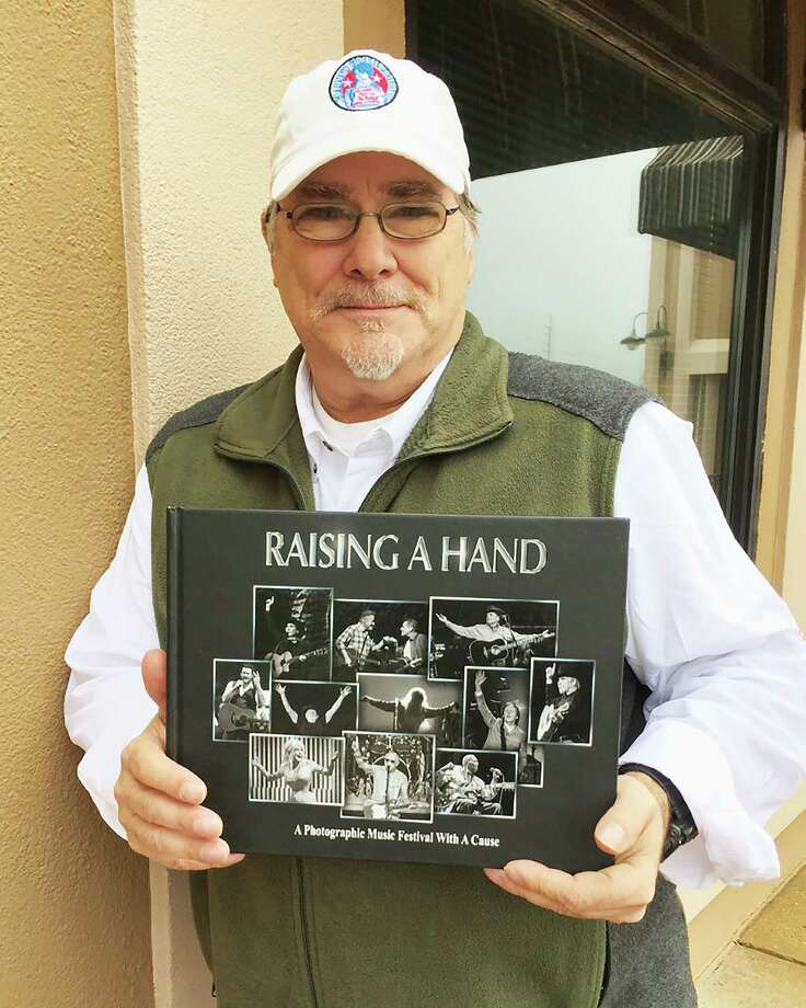 """Musician and photographer Kevin Black is holding the book """"Raising a Hand for Rett."""" Black lost his 16-year-old daughter Cortney to Rett Syndrome in 2003. Photo: Courtesy Photo"""