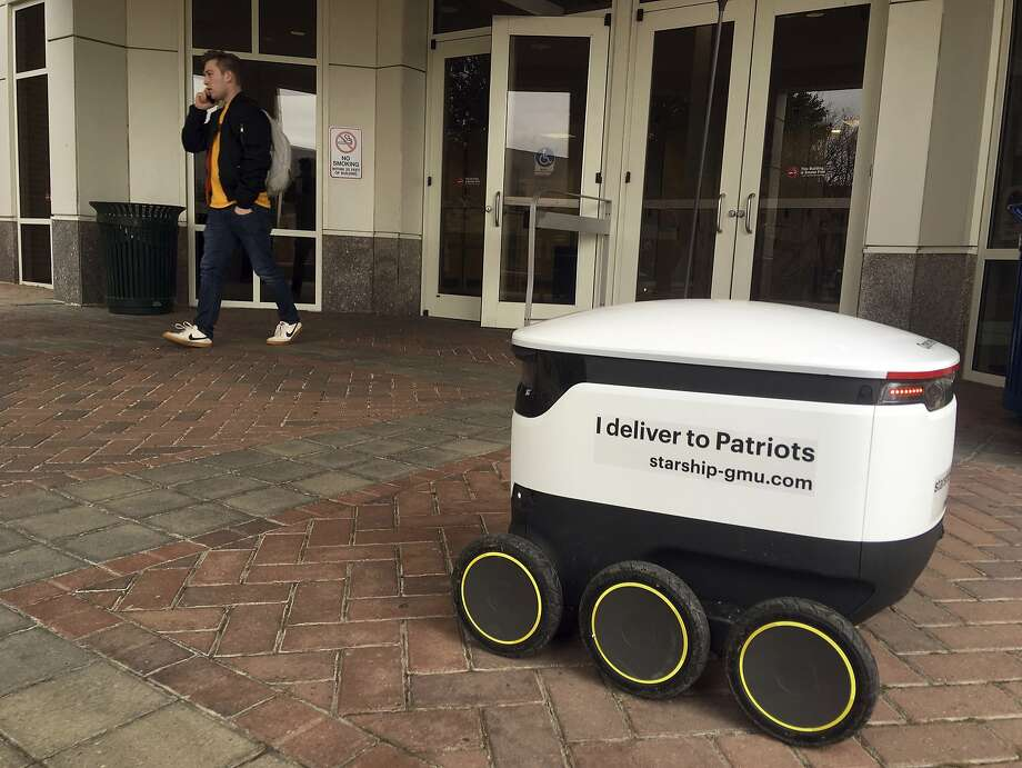 A Starship robot can carry orders of pizza, doughnuts and coffee to students at George Mason University in Fairfax, Va., for a $1.99 delivery fee. Photo: Matthew Barakat / Associated Press