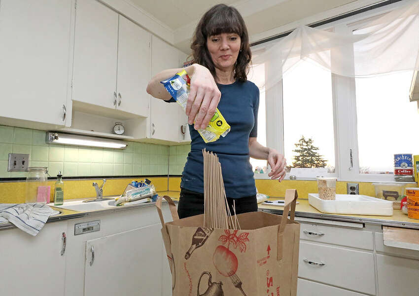 Bethany empties pasta into a food composting bag. Bethany Jean Clement cleans out her kitchen cupboards with the help of food waste expert Jill Lightner, getting in-depth about what you really should and shouldn't throw away. Photos taken Friday, Jan. 11, 2019 at Bethany's home. (Greg Gilbert/Seattle Times/TNS)