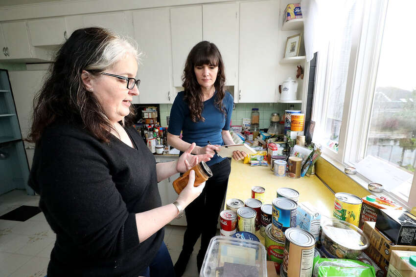 Food waste expert Jill Lightner, left, discusses what to keep and what to throw away with Bethany, center. Bethany Jean Clement cleans out her kitchen cupboards with the help of food waste expert Jill Lightner, getting in-depth about what you really should and shouldn't throw away. Photos taken Jan. 11, 2019 at Bethany's home. (Greg Gilbert/Seattle Times/TNS)