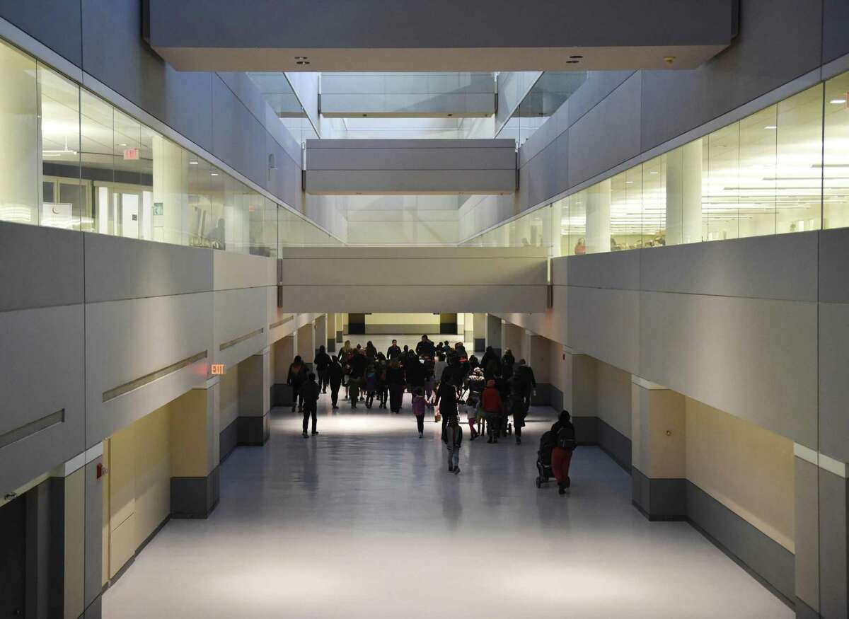 Parents and students walk through what will be the gymnasium area during an open house for the new Westover Magnet Elementary School, dubbed Westover @ 1 Elmcroft, in the Harbor Point neighborhood of Stamford, Conn. Tuesday, Nov. 13, 2018. Students were required to relocate after a severe mold problem was found in the school, so kids will now attend school in an office building with certain floors repurposed to suit students' learning needs.