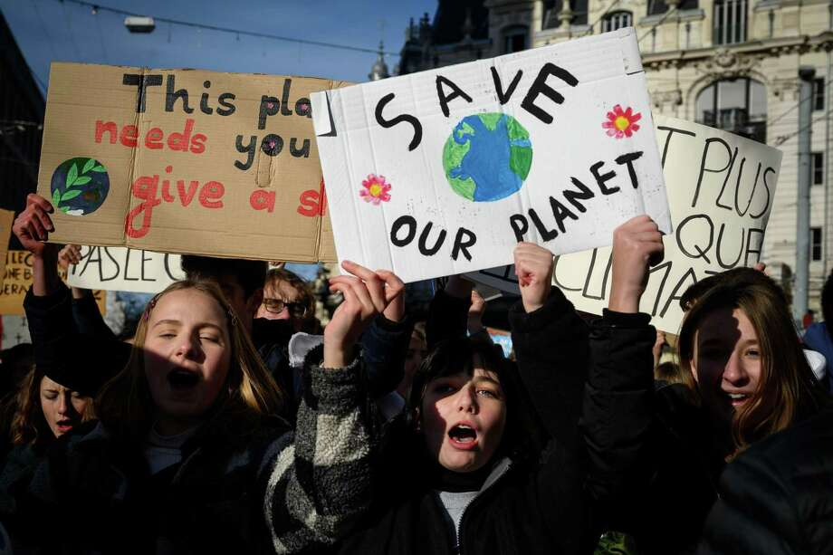 """Students show placard reading """"Save our planet"""" in a protest against climate during a strike on Friday, in Lausanne. A reader wonders why he should worry about climate change if the world will end in 12 years, according to Alexandria Ocasio-Cortez. Photo: FABRICE COFFRINI /AFP /Getty Images / AFP or licensors"""