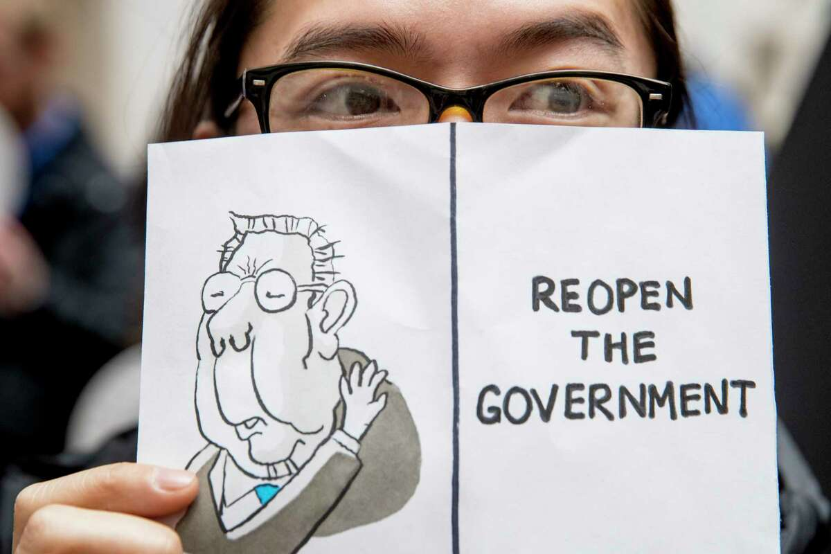 A furloughed government worker affected by the shutdown holds a sign that reads
