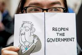 """A furloughed government worker affected by the shutdown holds a sign that reads """"Reopen the Government"""" during a silent protest against the ongoing partial government shutdown on Capitol Hill in Washington, Wednesday, Jan. 23, 2019."""