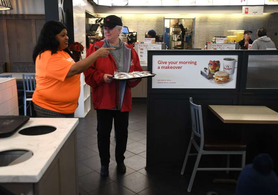 Kimberla Payton, left, gives Sue Little instructions on how to be a Chick-fil-A employee at the fast food restaurant on Tuesday. Little, the principal at Bingman Elementary school, and Payton traded jobs for part of the day as part of a BISD event to illustrate collaboration between the district and business. Other schools and businesses also took part in the event. 