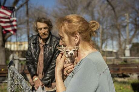 James Red Cloud Hill and his wife Earla Red Cloud Hill and their dog Babie are recipients of a Meals on Wheels pet food delivery program known as AniMeals, which provides foods to clients' pets.