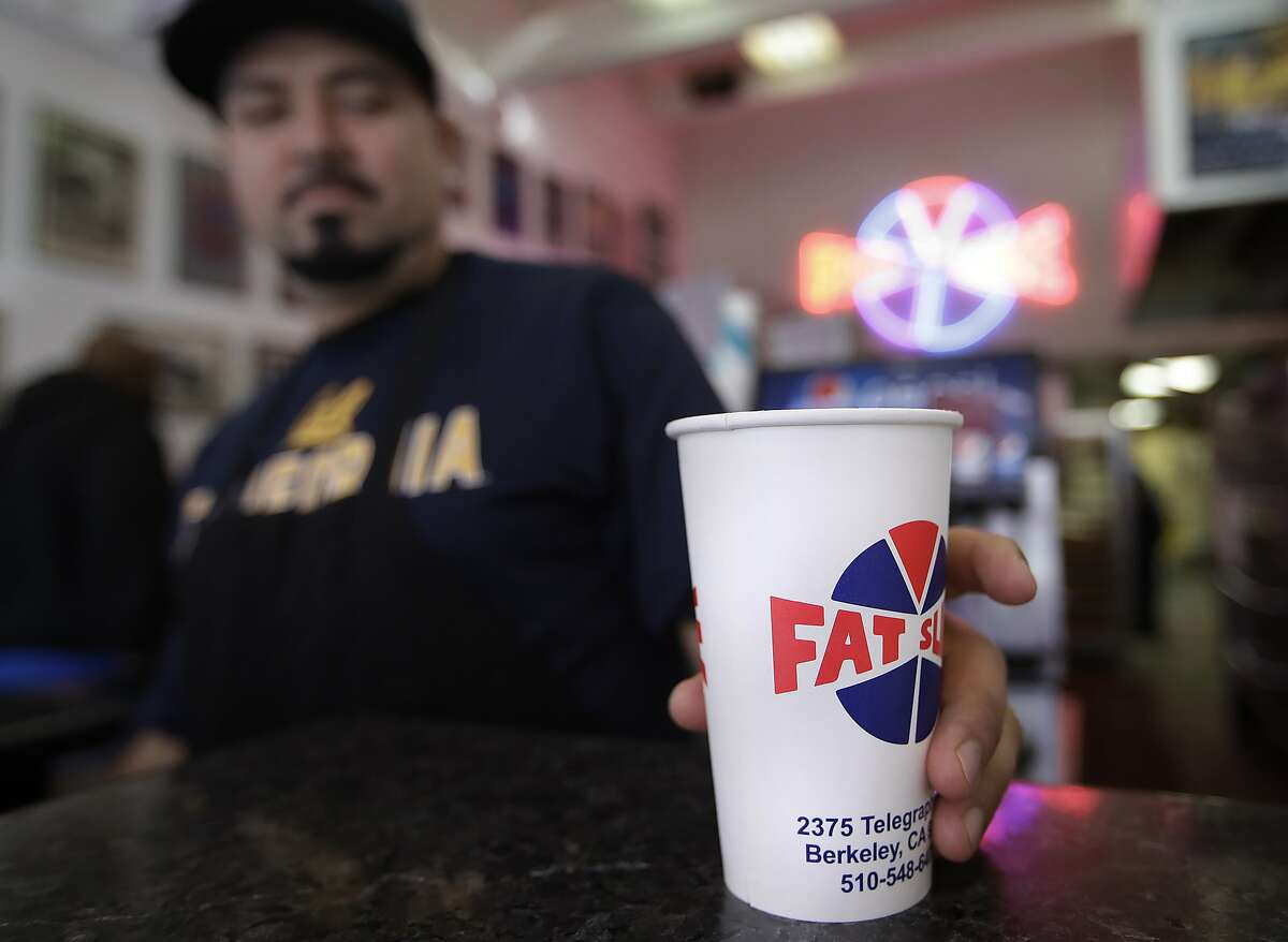 Fat Slice pizza employee Gustavo Munoz places a disposable cup on a table Wednesday, Jan. 23, 2019, in Berkeley, Calif. Berkeley has approved a 25-cent tax on disposable cups city officials say is part of an effort to eliminate restaurant waste. The City Council voted unanimously Wednesday to approve the ordinance that also forces restaurants to provide to-go containers that are compostable by January 2020. (AP Photo/Ben Margot)