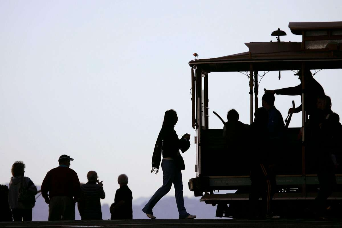 Visitors, at left, get a view of the city from a hilltop as the Powell-Hyde cable car line goes by at Hyde St. and Lombard St. in San Francisco, Friday, Oct. 10, 2008. (AP Photo/Marcio Jose Sanchez)