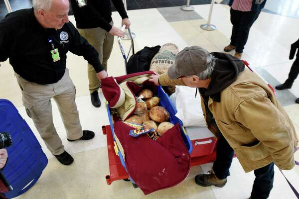 Gary Kleppel of Knox, right, displays a basket bread that he baked for Transportation Security Administration agents at Albany International Airport on Wednesday, Jan. 23, 2019, in Colonie, N.Y. Gary and his wife, Pam, delivered two cart-loads of food for the unpaid federal security workers. (Will Waldron/Times Union)