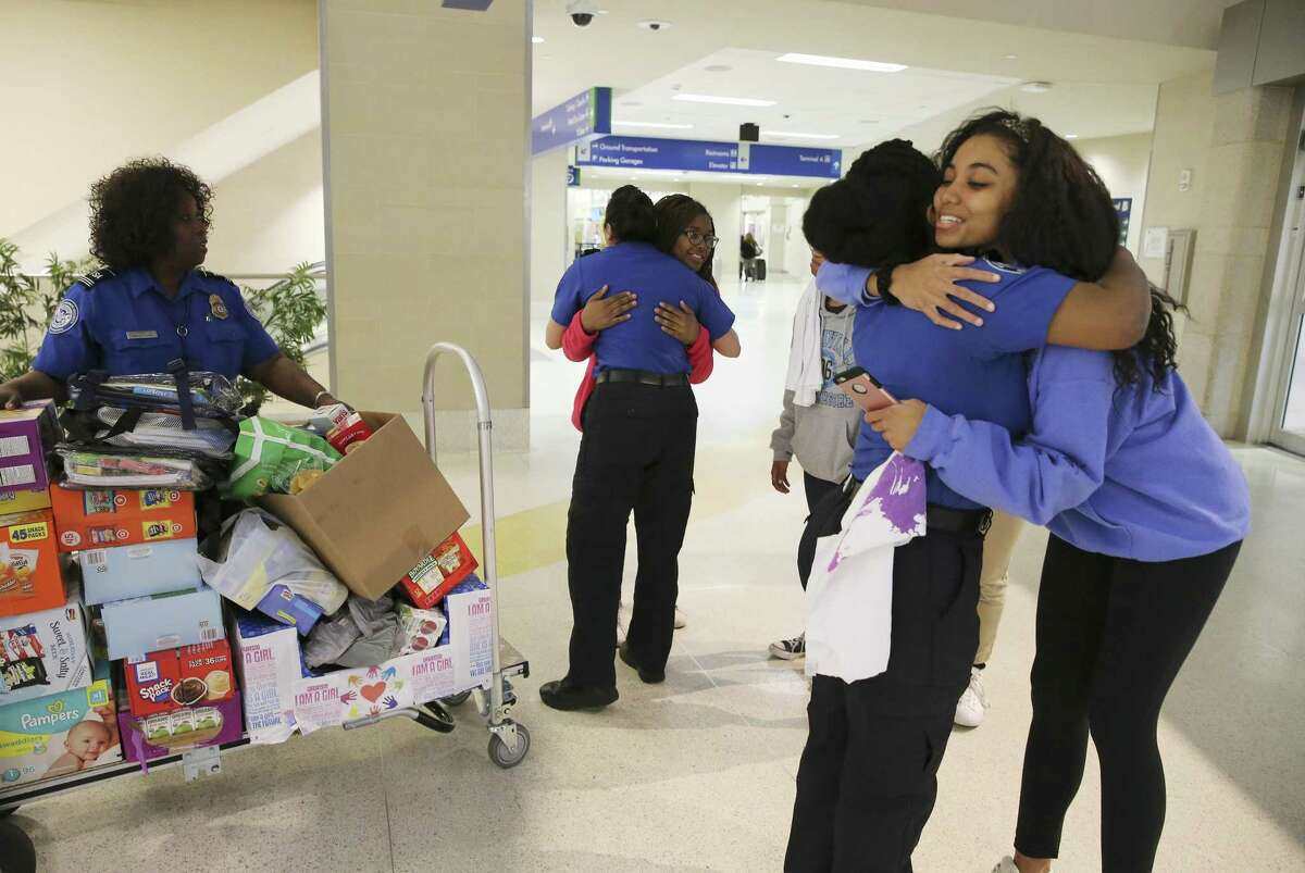 Reanna Wilson (right) of the local chapter of Girl Up gets a hug from TSA Lead Officer Chynae Raiford after the nonprofit group that empowers young women donated food and other items to help children of TSA government workers at the San Antonio International Airport on Wednesday, Jan. 23, 2019.