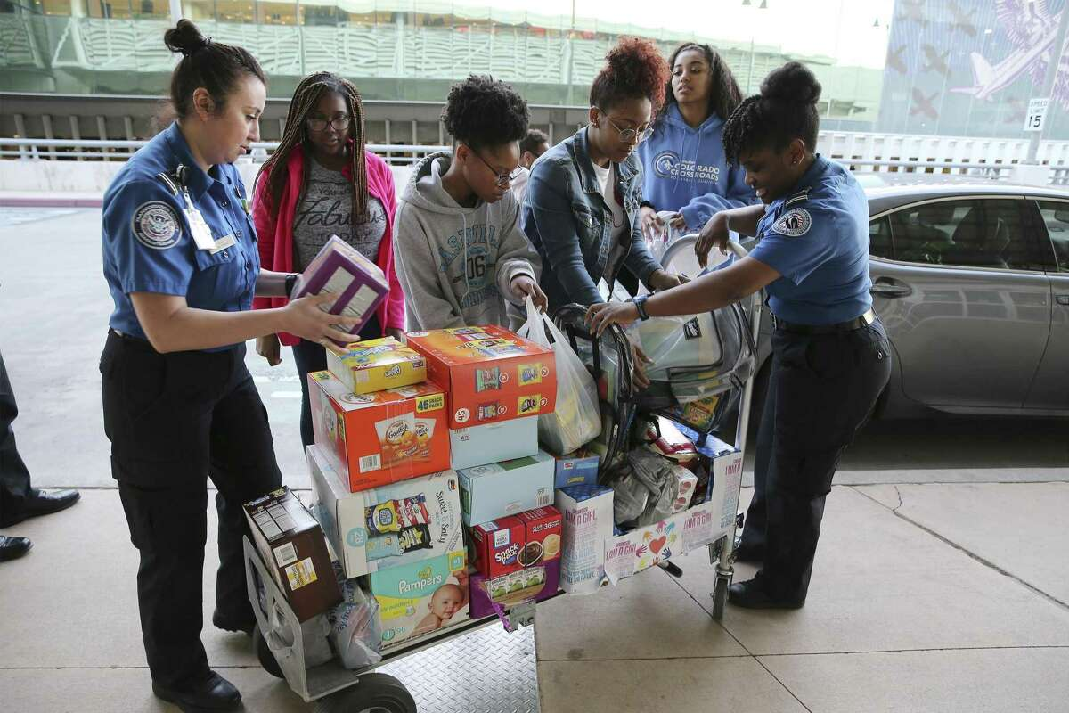 TSA Lead Officers Tiffany Rios (left) and Chynae Raiford (right) help load a cart with donated items from Brittney Carson (second from left), Simone Green, Jada Young and Reanna Wilson - all members of the local chapter of Girl Up, a nonprofit that empowers young women on Wednesday, Jan. 23, 2019. The donated food items and other supplies went to help children of TSA government workers at the San Antonio International Airport. The four young women from the local chapter along with two parent chaperones off-loaded a truckload of items received by two TSA officers. With the government shutdown going on for more than a month, local TSA personnel were grateful for the donations which helps them and their families during the shutdown. (Kin Man Hui/San Antonio Express-News)