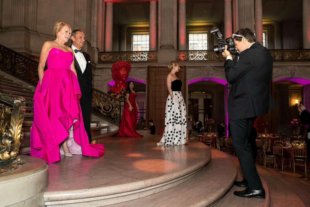 """San Francisco Ballet Opening Night Gala event chair Claire Kostic (left) and Mark Kostic pose for a photograph by society photographer Drew Altizer (right) during the event at City Hall in San Francisco, Calif., on January 23, 2019. The theme of the evening was """"This is Passion."""""""