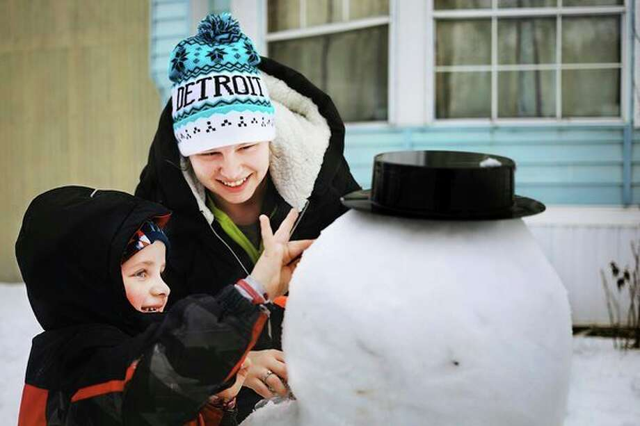 Courtney Lutz, center, helps her son, Jordan Laney, 4, to build a snowman outside of their home on Wednesday afternoon in Midland. (Katy Kildee/kkildee@mdn.net)
