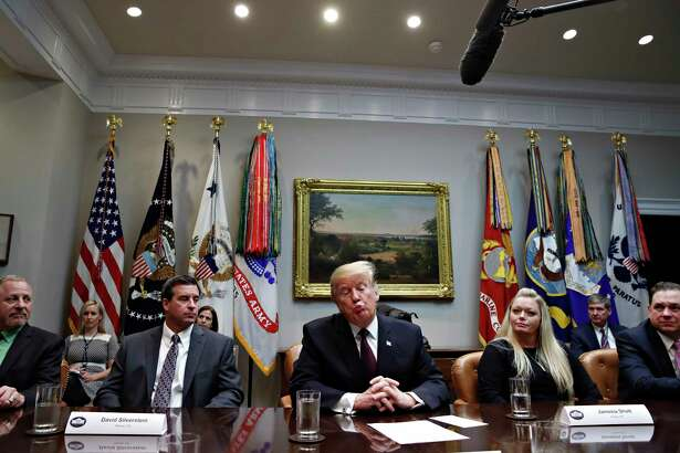 President Donald Trump, center, reacts as he is told by a reporter that House Speaker Nancy Pelosi of Calif., said the Democratically controlled House won't pass the required measure for him to make the State of the Union address at the Capitol until after the government is fully opened, during a healthcare roundtable in the Roosevelt Room of the White House, Wednesday, Jan. 23, 2019, in Washington. With the president are David Silverstein, of Denver, left, and Jamesia Shutt, of Aurora, Colo., right.