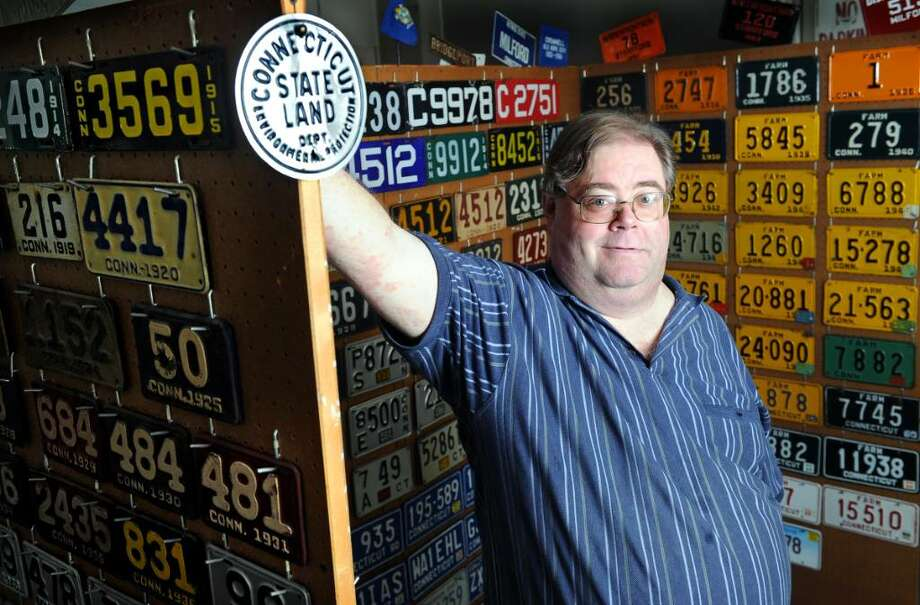 David Kuehne stands among a small fraction of the Connecticut license plates that make up his massive collection Tuesday July 20, 2010 at his Milford home.  Kuehne has over 2000 plates from all over the country but focuses his collection on Connecticut plates. Photo: Autumn Driscoll / Connecticut Post