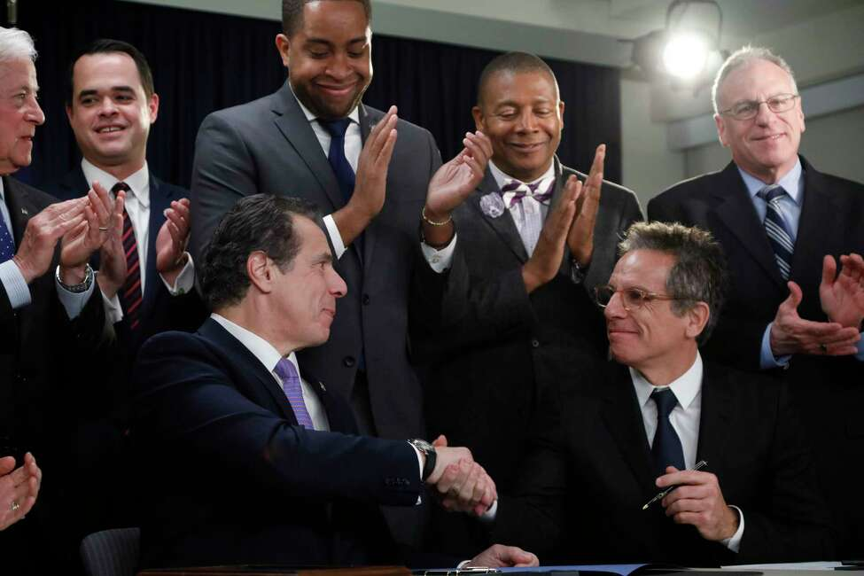 New York Gov. Andrew Cuomo, left, and actor Ben Stiller shake hands after the governor signed a bill into law to allow for early voting, Thursday, Jan. 24, 2019, in New York. The bill will allow New Yorkers to cast a ballot before Election Day in a bid to improve its low voter turnout rates. Stiller had lobbied for the new law.